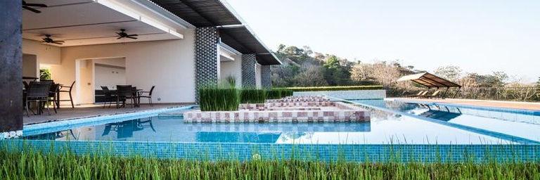 Area social con piscina infinita con vista a las montañas